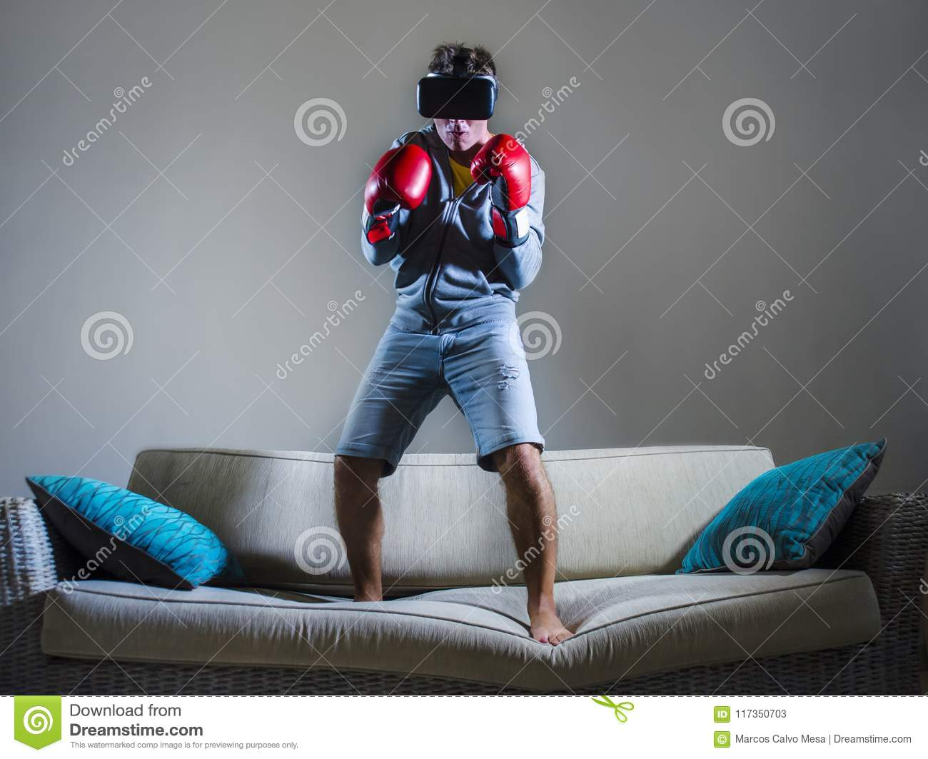 4d3412cd615 Young gamer man using VR goggles headgear and boxing gloves playing  simulator 3D fight video game having fun on home sofa couch enjoying  exciting virtual ...