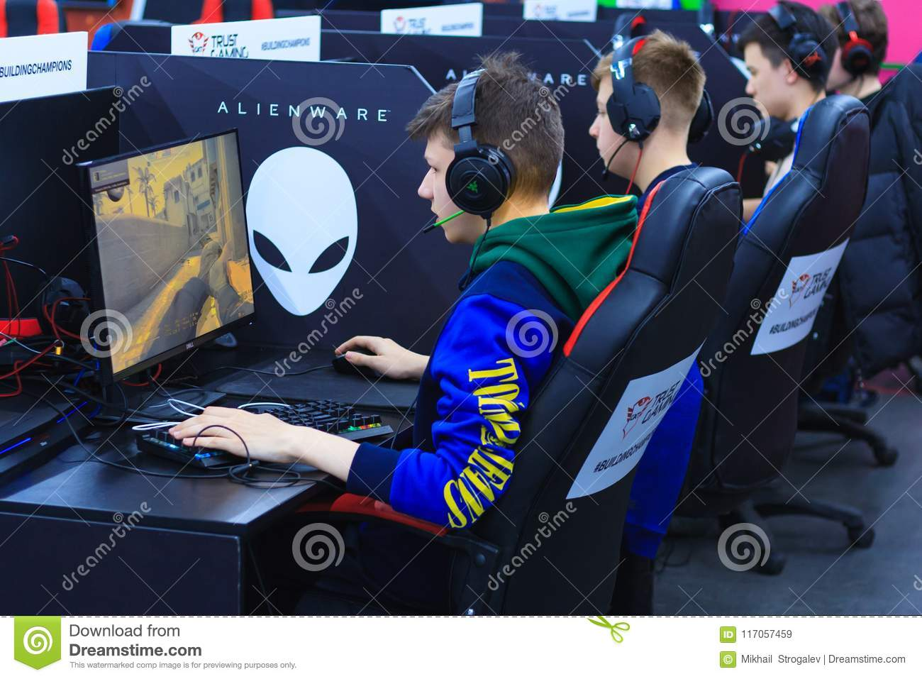 Young gamers in headphones playing at the computer