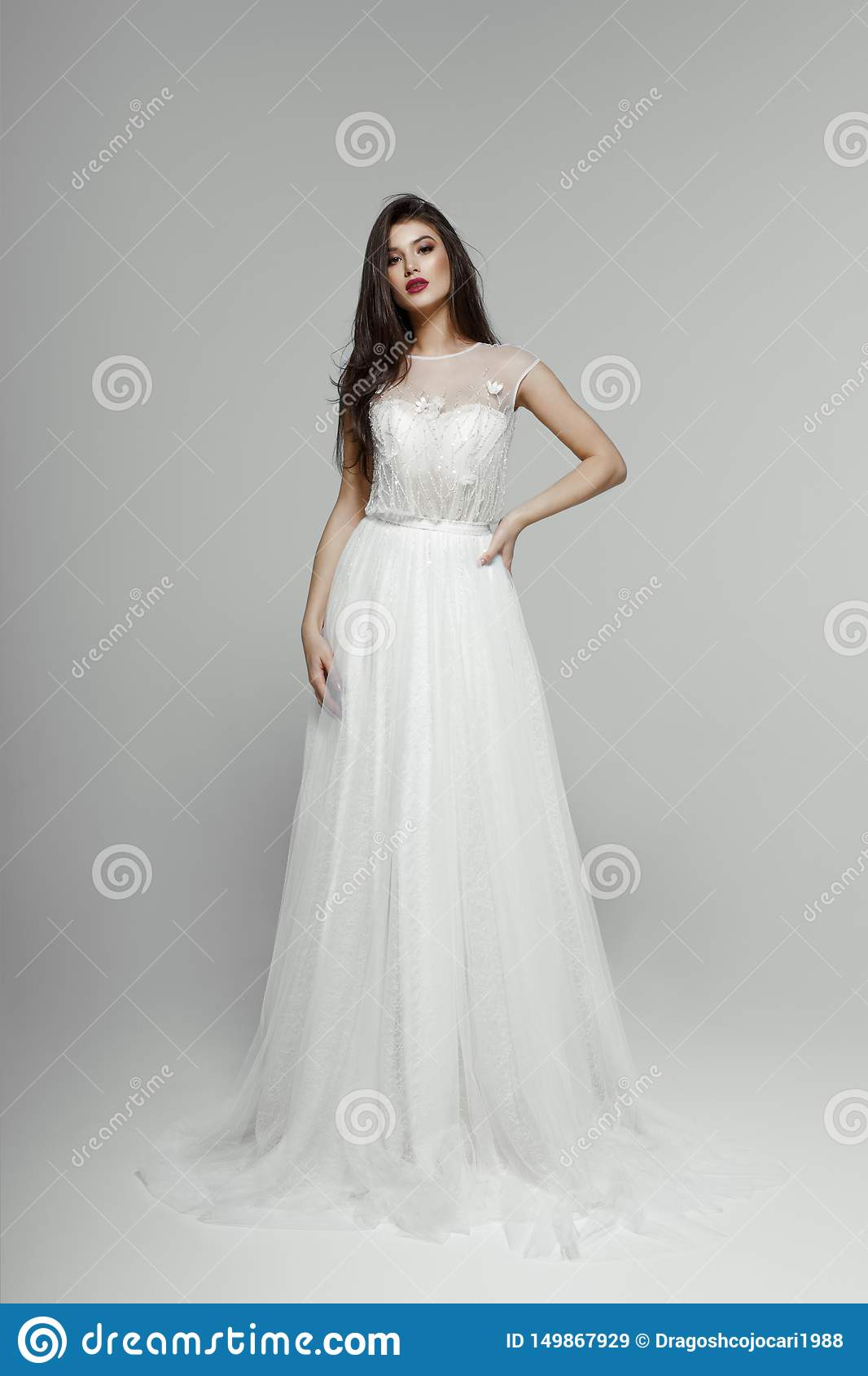 Fashion model in wedding dress. Young Sensual Bride In White dress. Looking at camera, isolated on a white background.