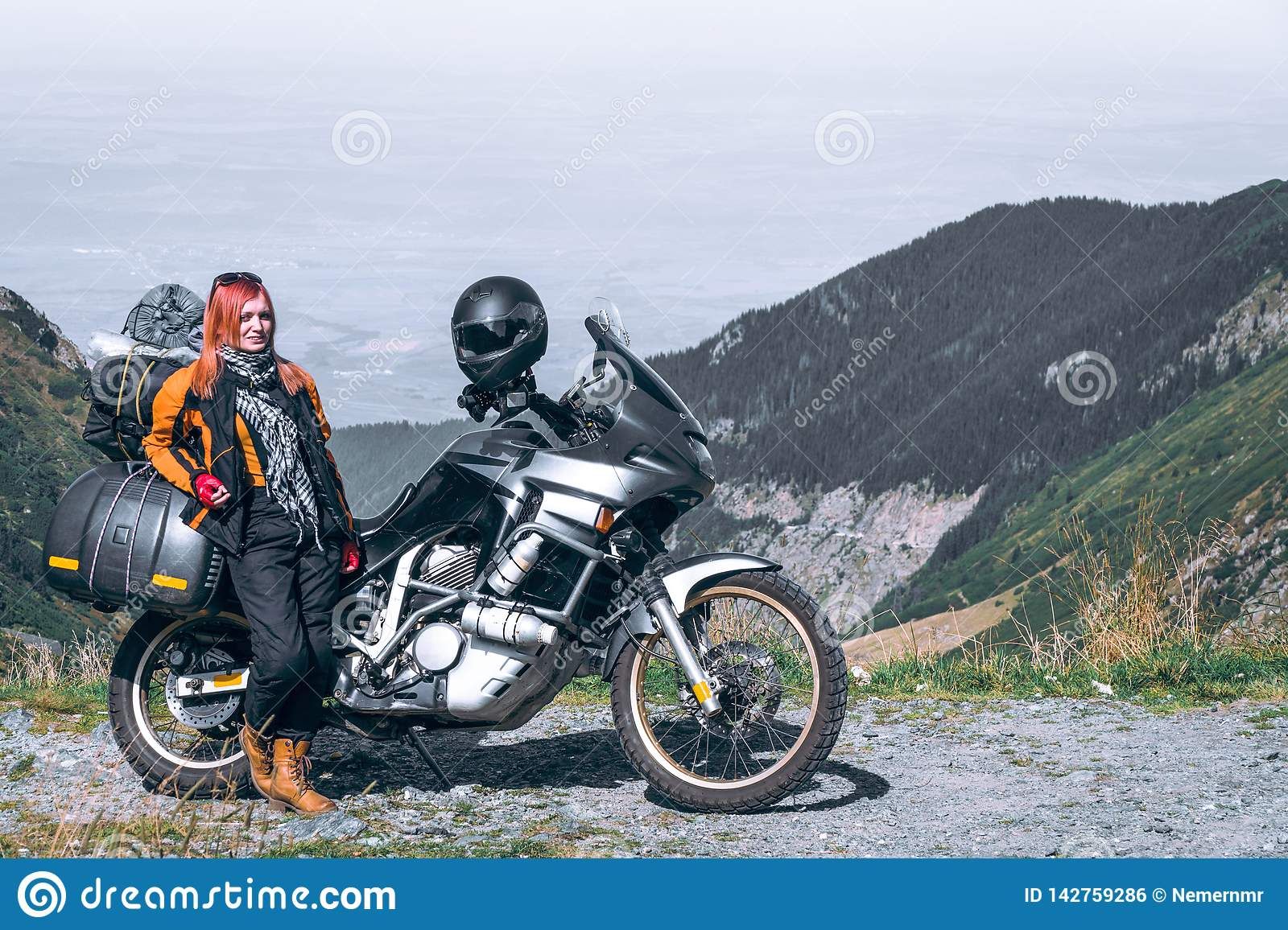 Young girl with adventure motorcycle. woman rider. Top of the mountain road. Motorbike vacation. Travel and active lifestyle