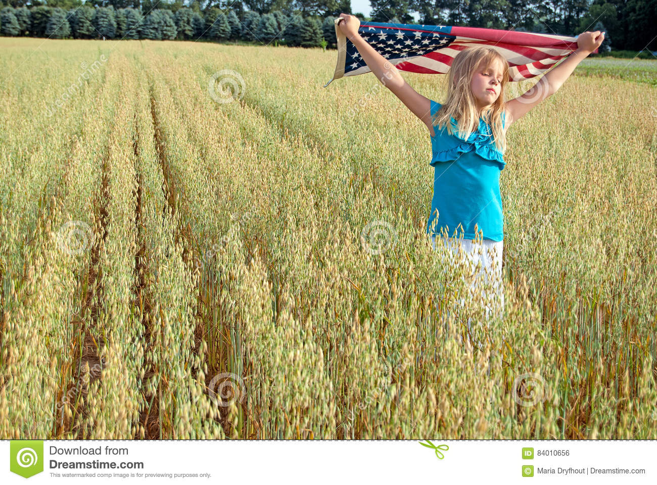 Young girl with American flag in field