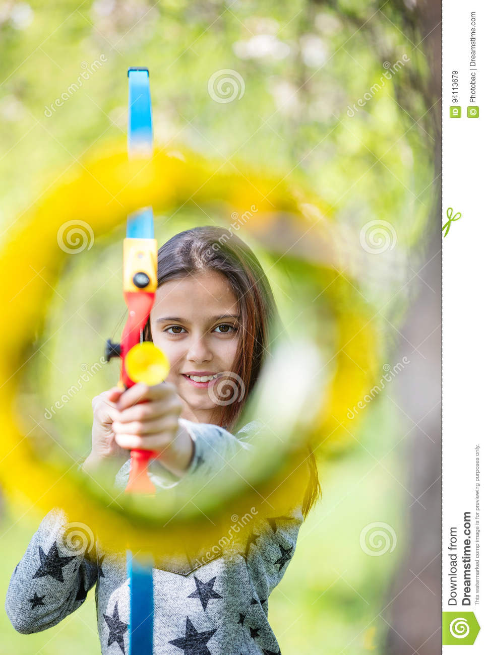 Young girl archer with bow aiming through flower wreath