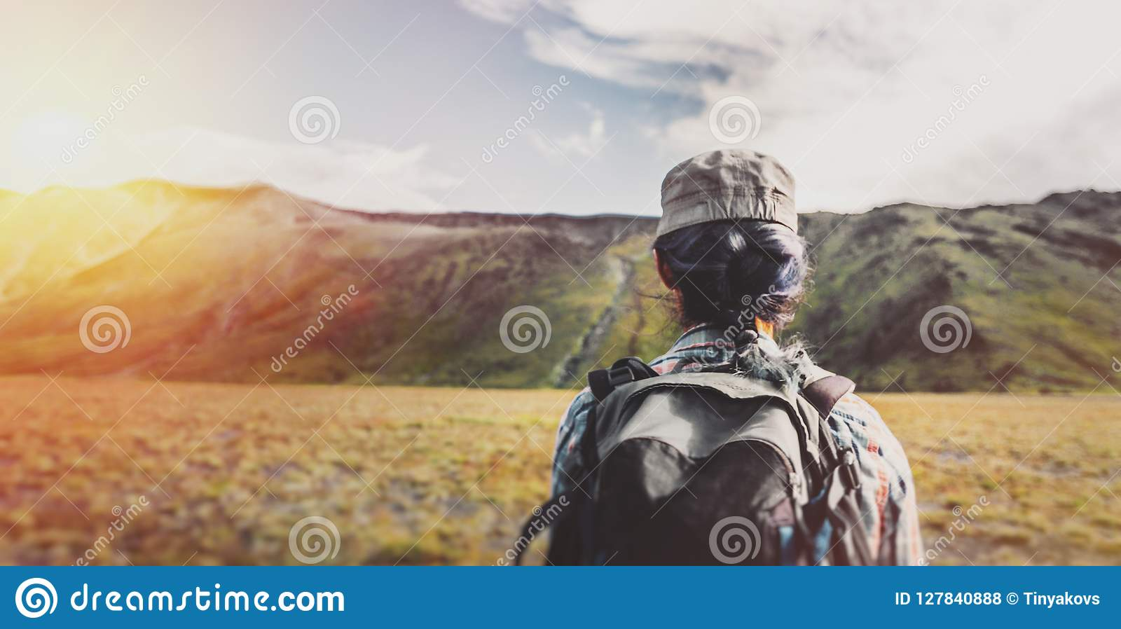Young girl with backpack hiking in the mountains in the summer