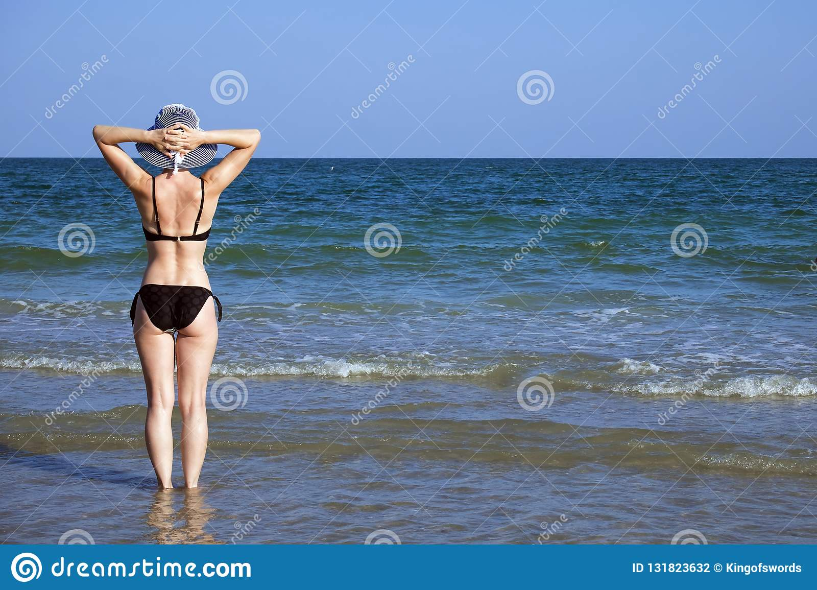 83ecd0c35d661 Young girl in a bathing suit and a striped hat is standing in the sea  holding