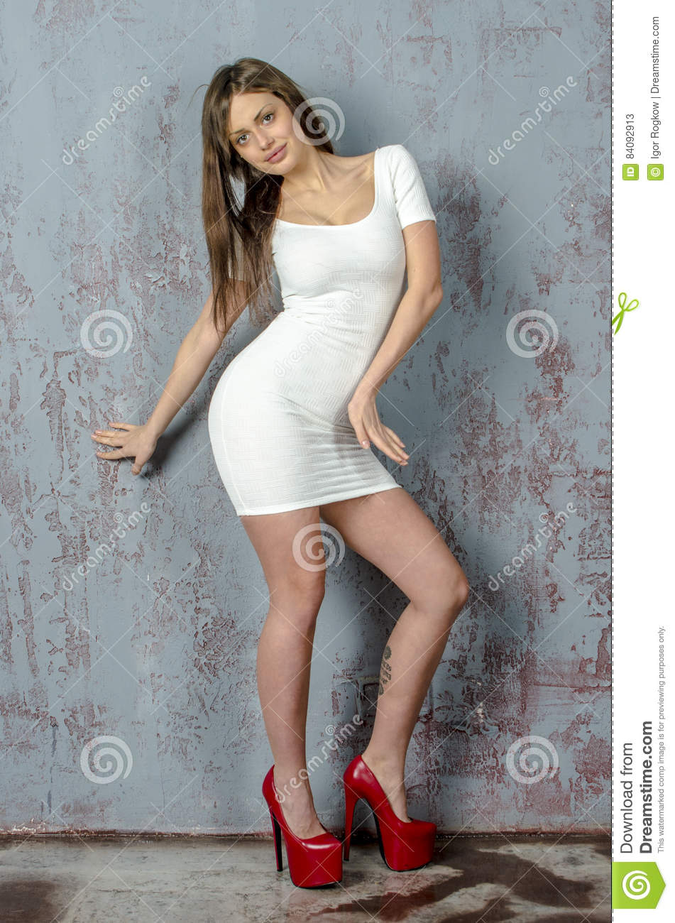 Young girl with a beautiful figure in a trendy white dress
