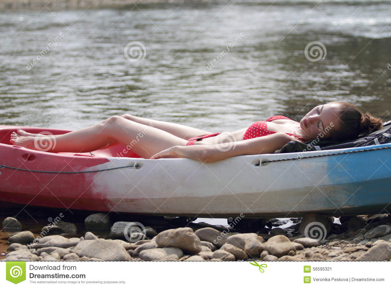 A young girl in bikini lying on the boat and sunbathing near the river, enjoying holidays in Laos