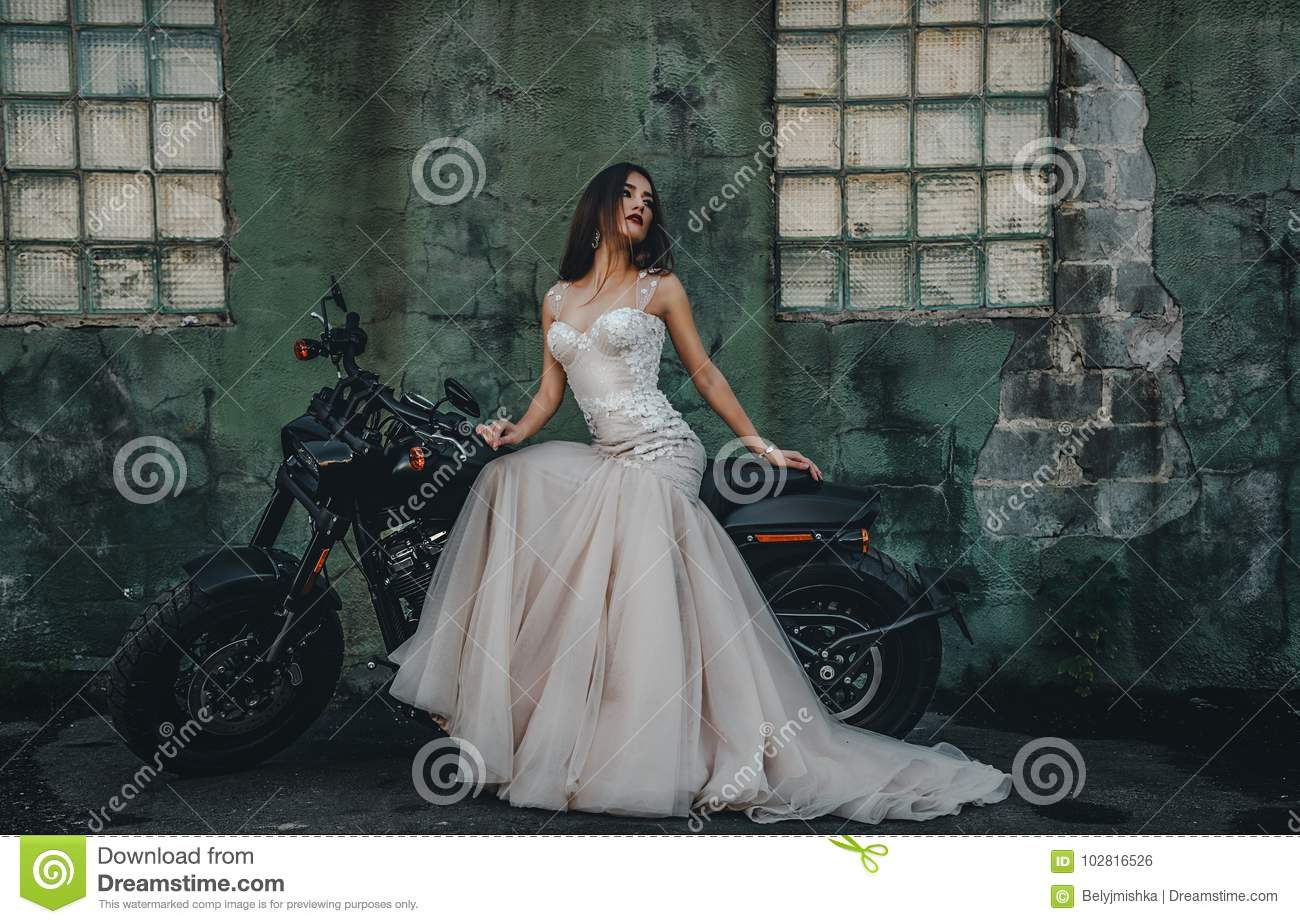 Young girl bride on a new man`s motorcycle.