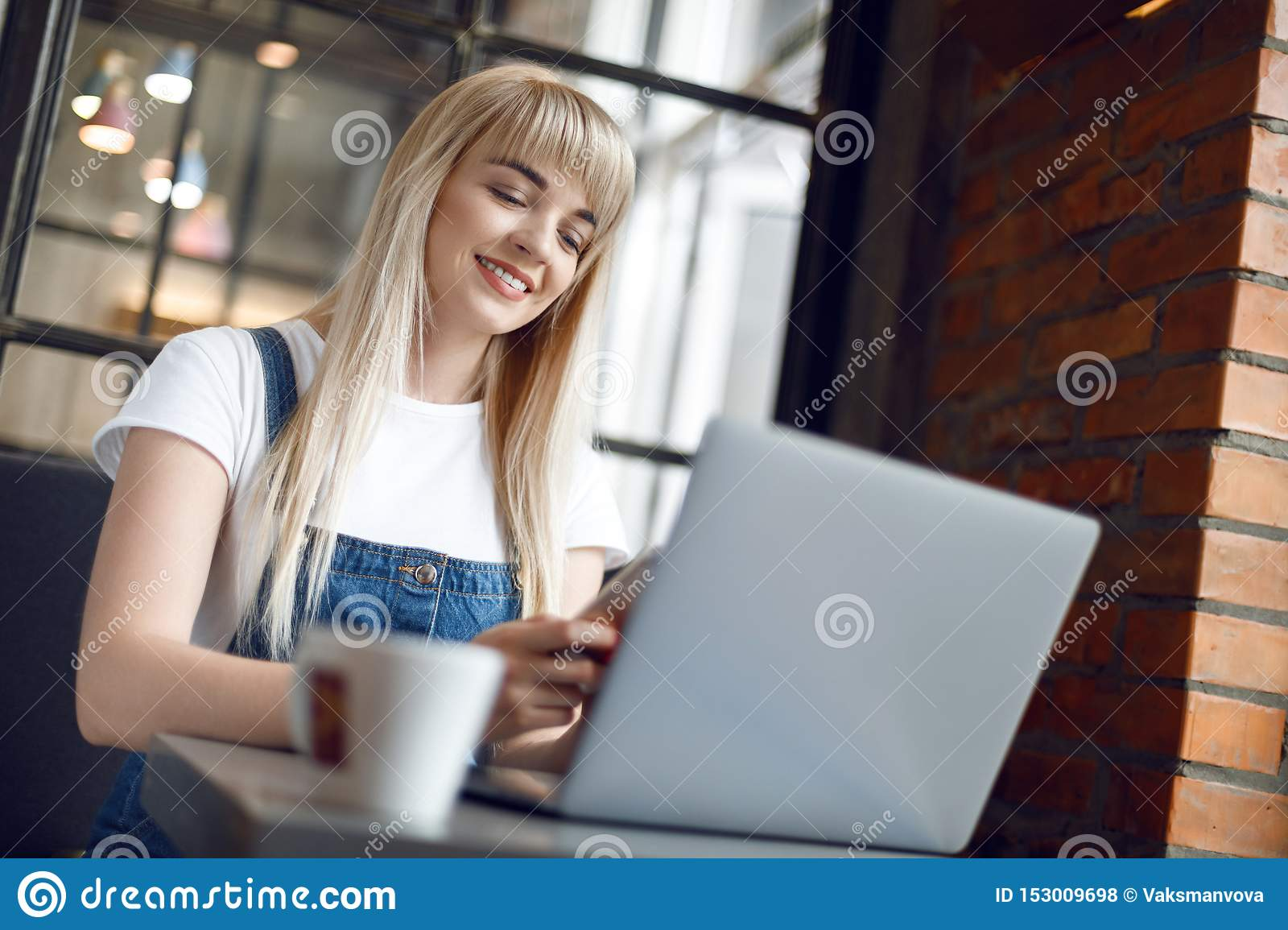 Young girl at cafe drinking coffee and using mobile phone. Online shopping