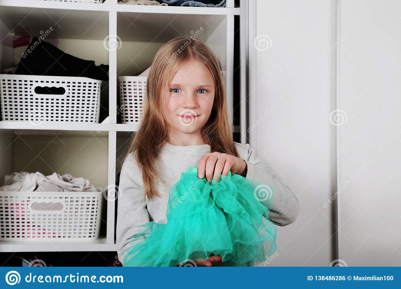 Young girl choosing dress in wardrobe at home. The wardrobe which put in order. All things are folded neatly. Many boxes. Everythi
