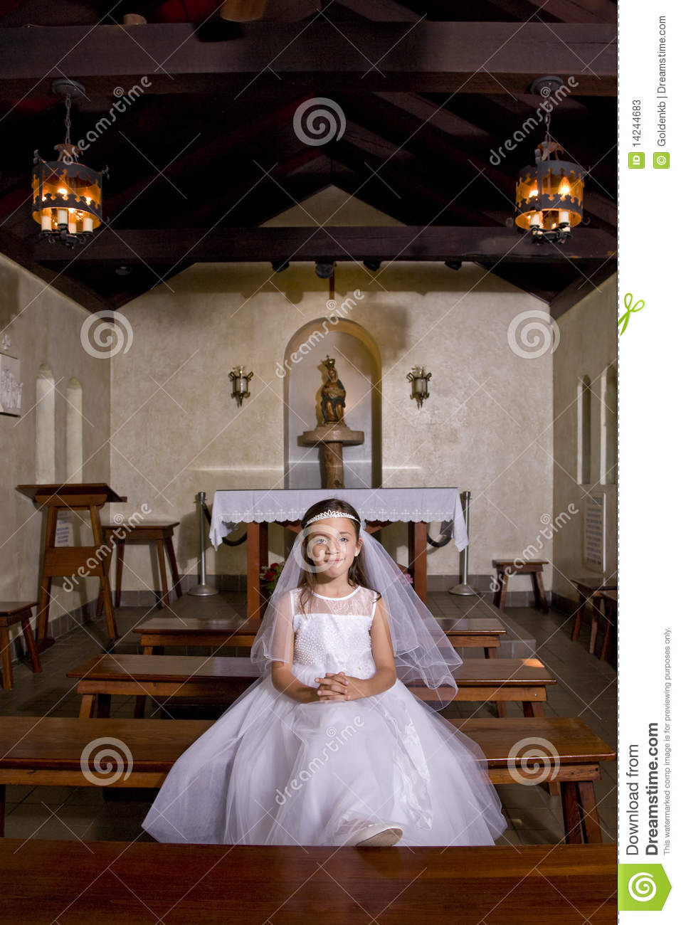 Young Girl In Church Wearing First Communion Dress Stock