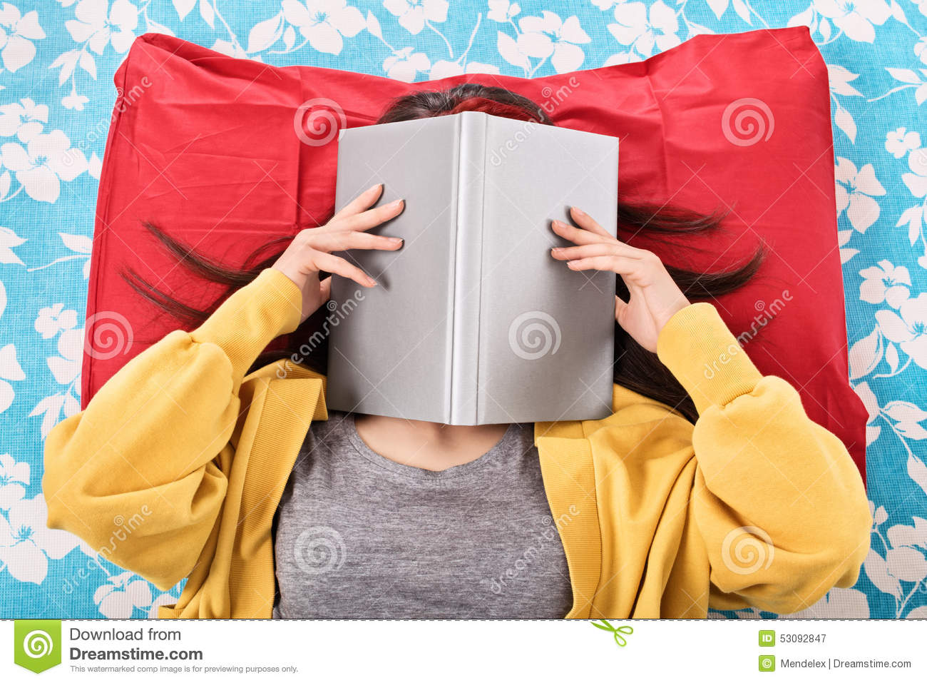 Book Covering Face : Young girl covering her face with an open book stock image