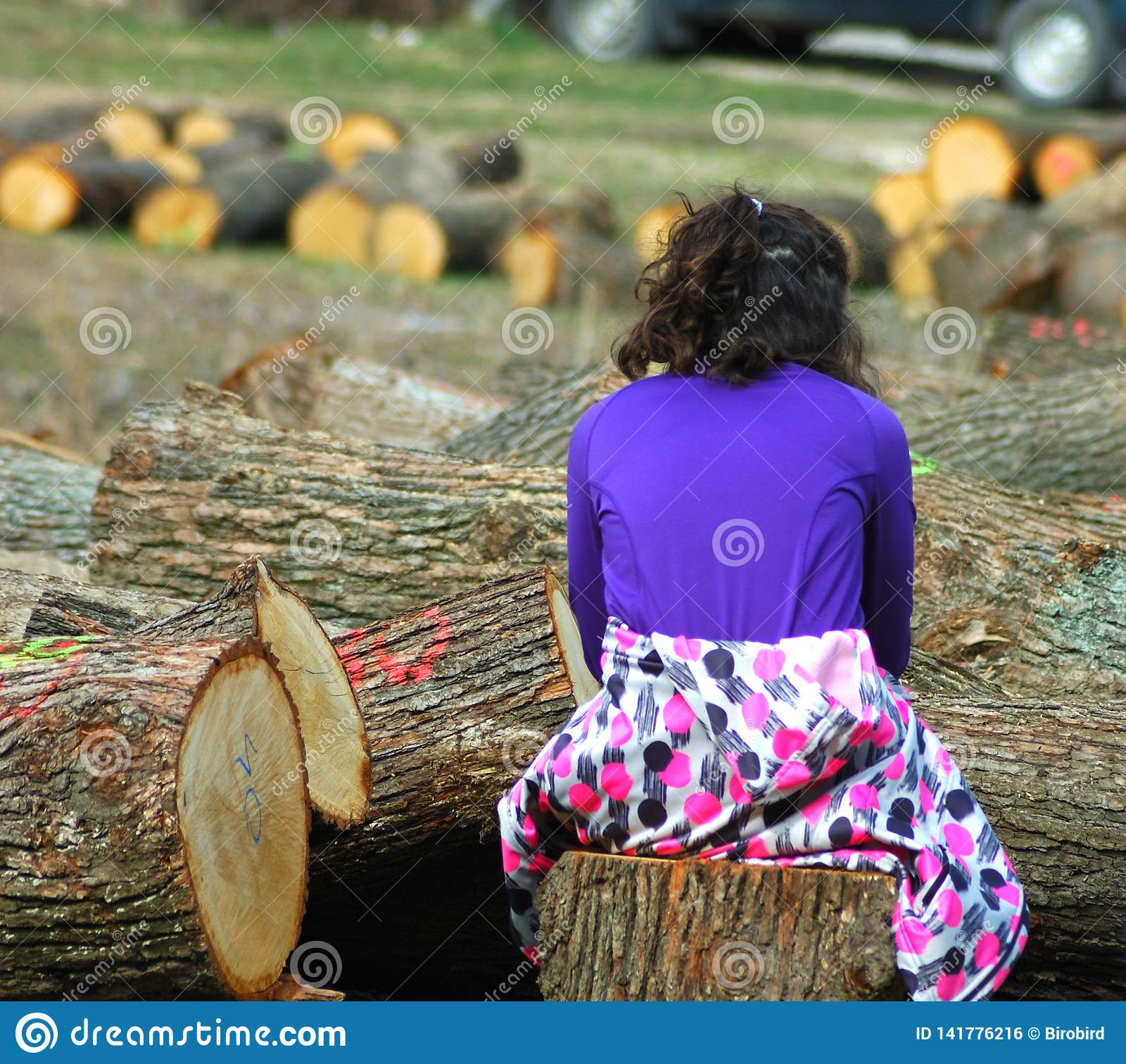 Young girl between cutted tree