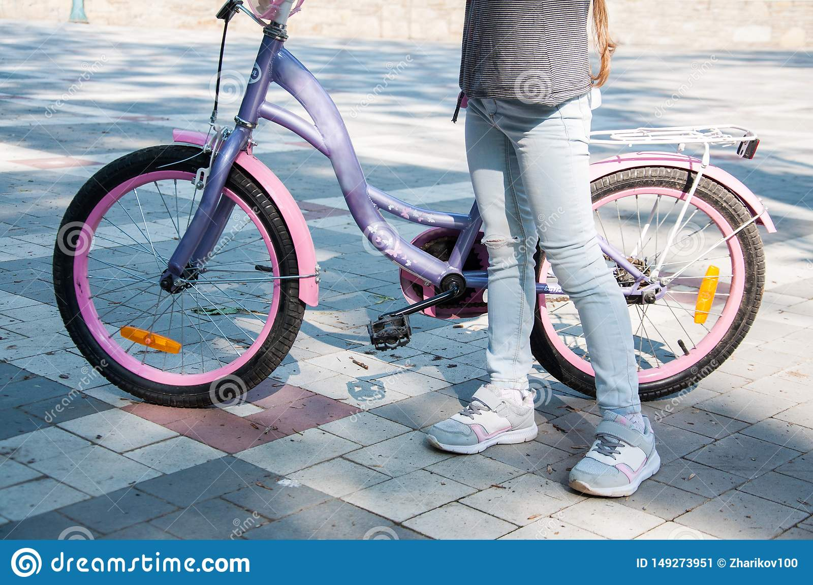 Young girl in denim pants stands near the bike holding it.