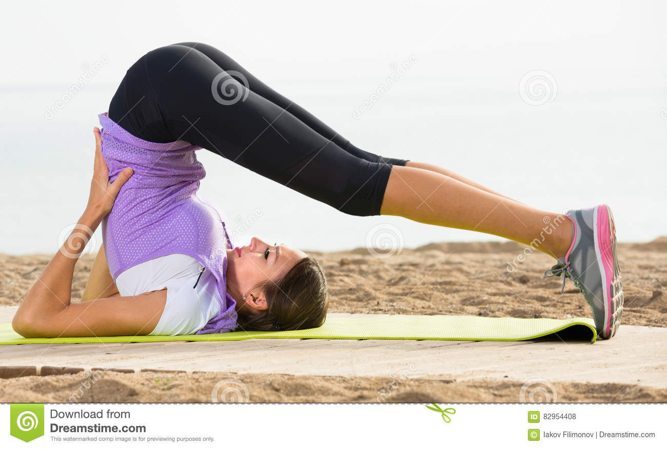 Young Girl Doing Yoga Poses Sitting On Sunny Beach Stock Photo