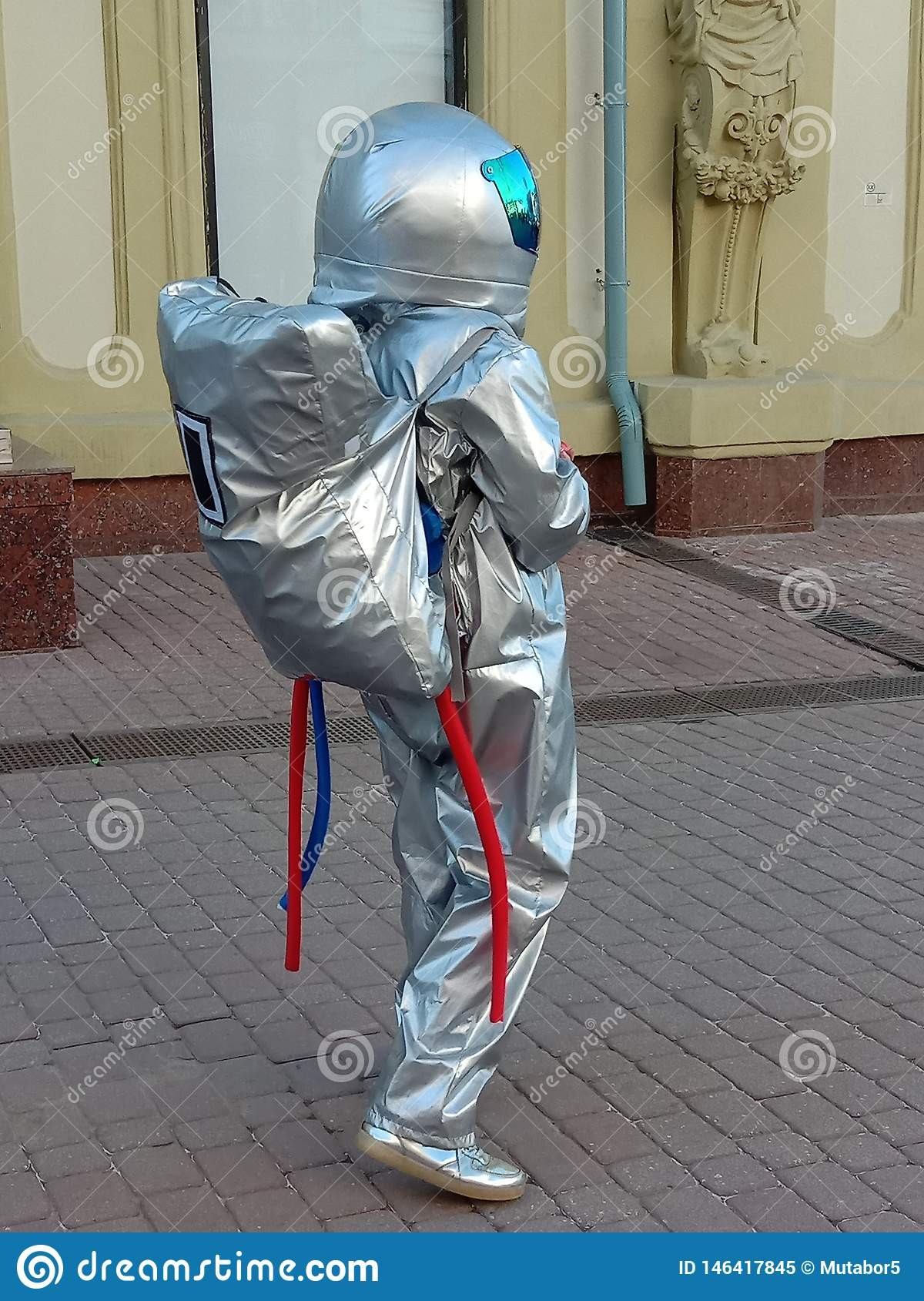 A young girl dressed as an astronaut distributes ads on a pedestrian street in the city. Promotion of services.