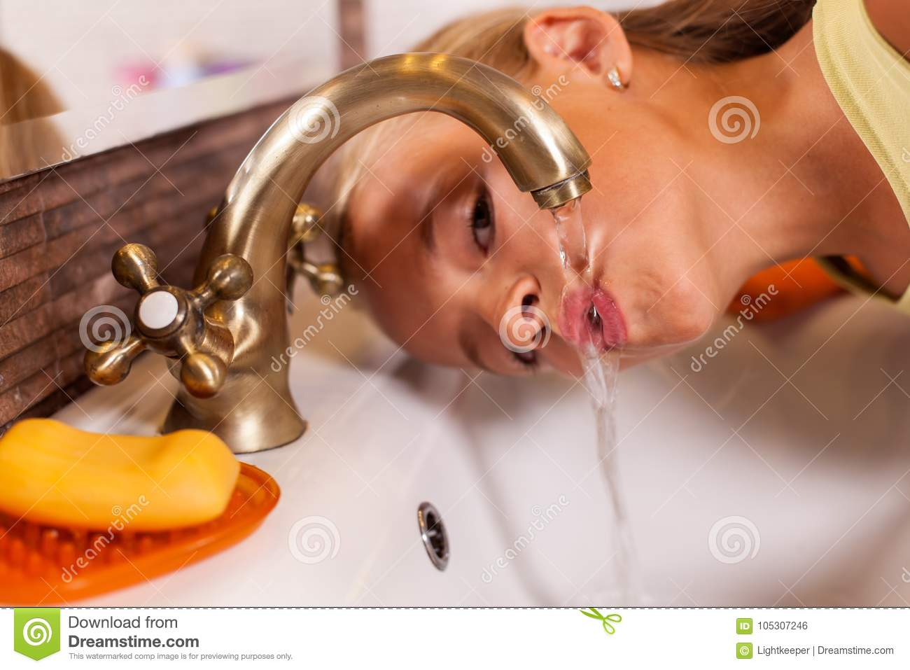 Young girl drinking from the bathroom faucet