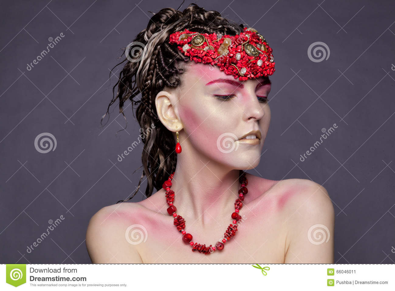 Young girl in earrings and necklaces of red coral