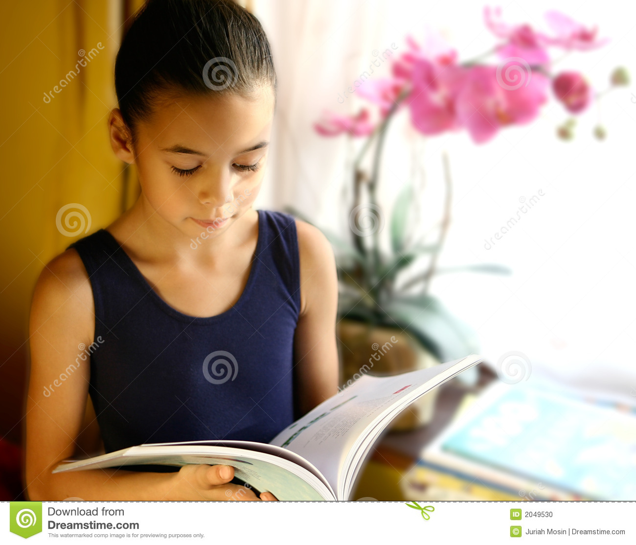 A Young Girl Engross In Her Reading Stock Photo - Image ...