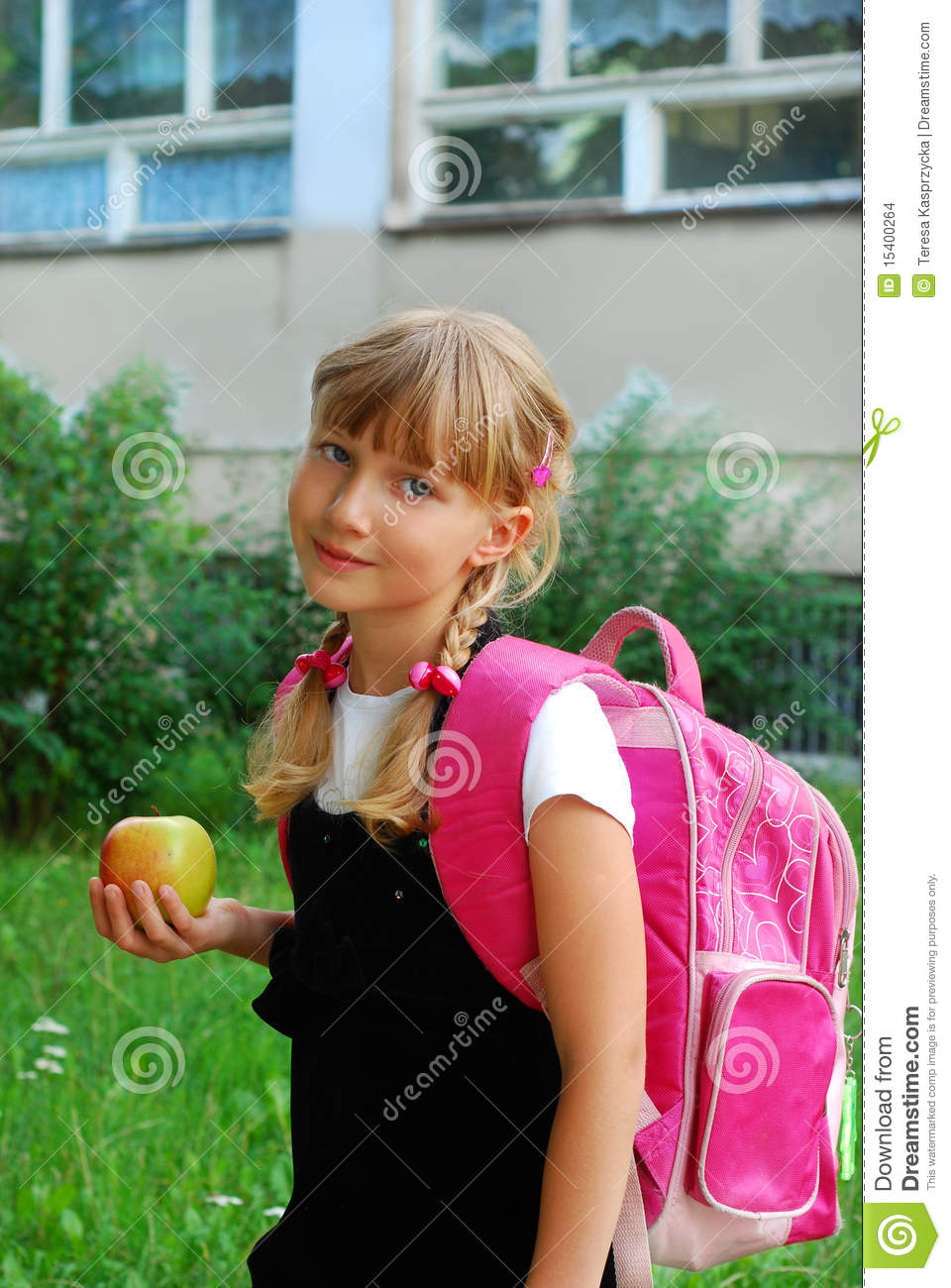Two smiling girls in uniform walking to school and