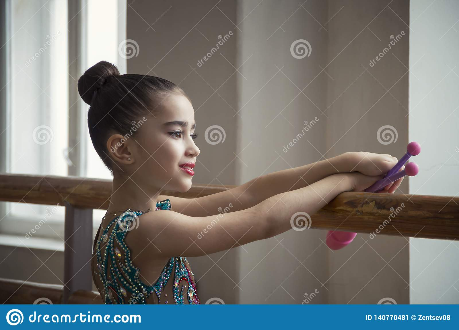Young girl gymnast with clubs looks through a large window in the hall for the horeography