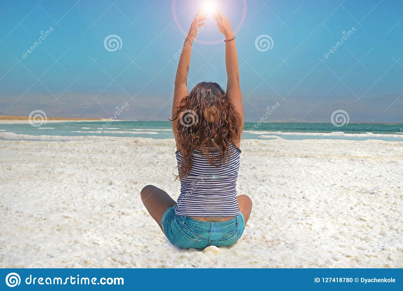 Young girl with her hands is catching the energy of the sun. long-haired girl sits on the shore of the Dead Sea in Israel