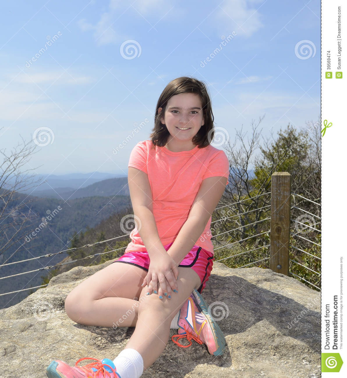young girl resting on a rock overlook along a hiking trail.