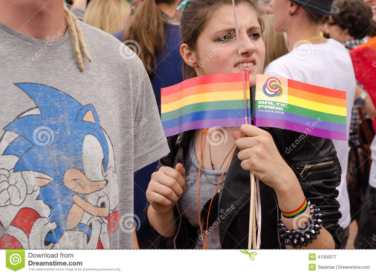 VILNIUS, LITHUANIA - JULY 27: young nice girl hold in hand two rainbow  paper flag on July 27, 2013 in VILNIUS, Lithuania. Annual biggest baltic gay  pride ...