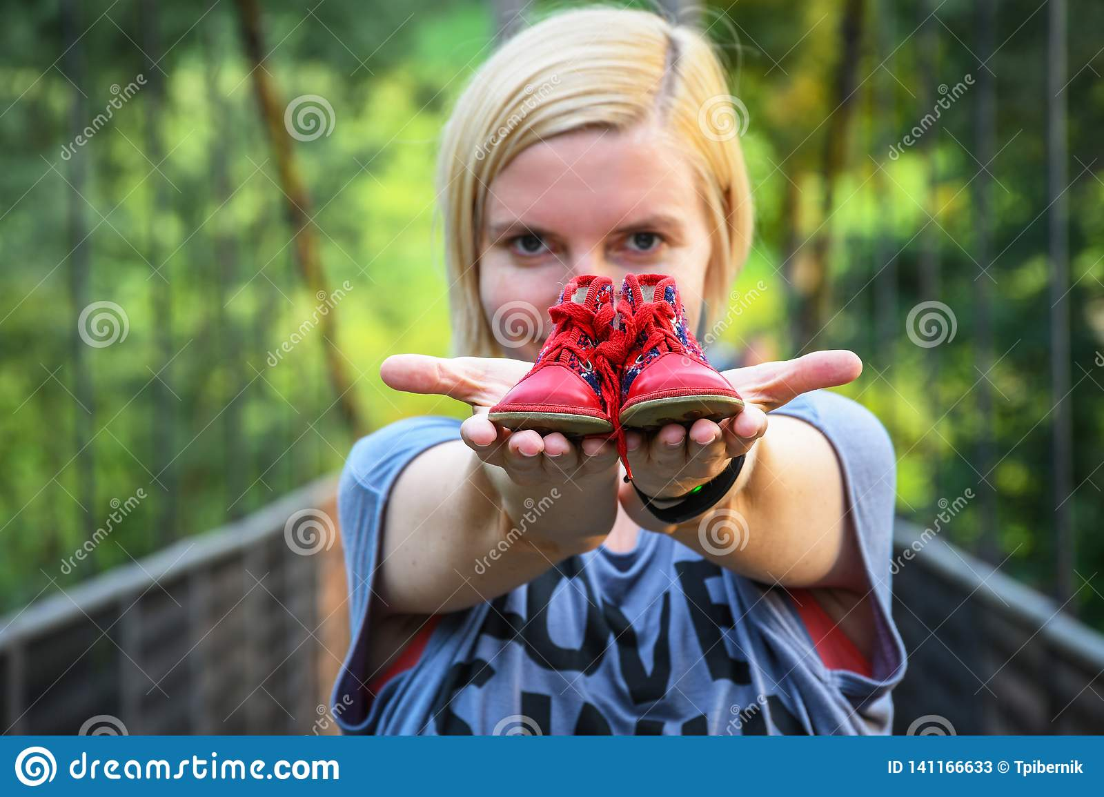 Young girl holding in both extended arms small red baby shoes