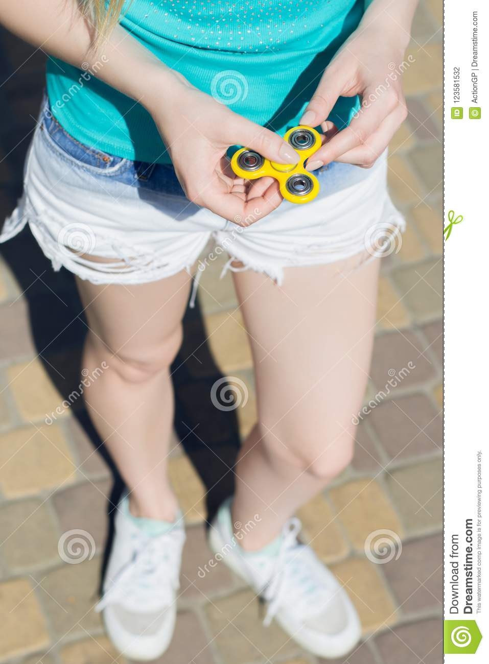 Young girl holding fidget spinner in hands while having a walk outdoors  addiction game gamer play player yellow thing toy cropped close up pov  point of view ...