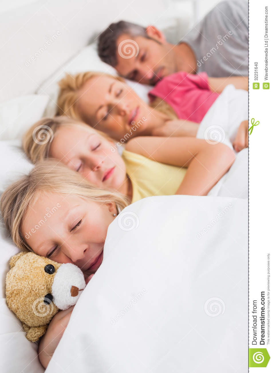 Young Girl Holding A Teddy Bear Next To Her Sleeping