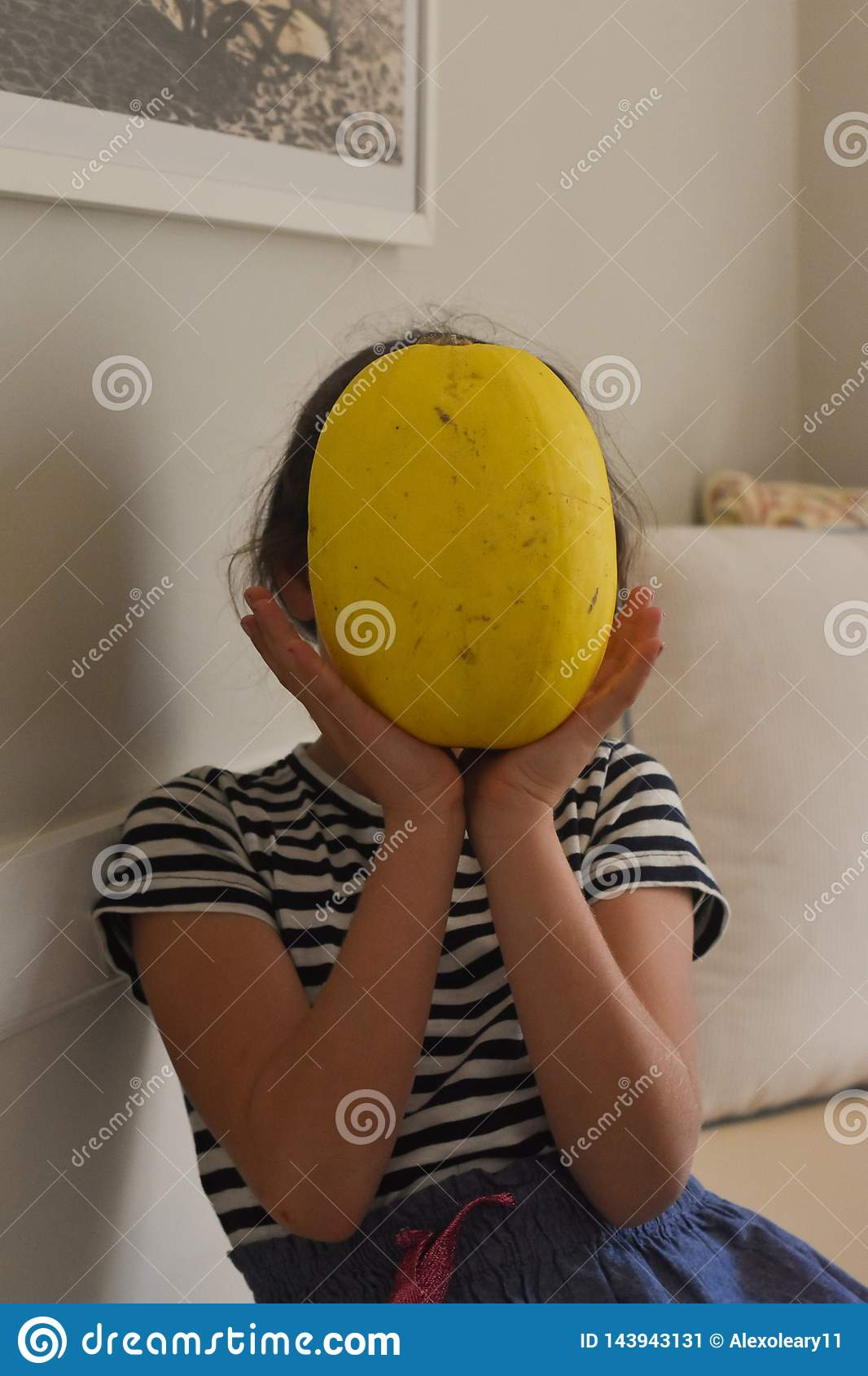 Young girl holding vegetable infront of face in a white living room.