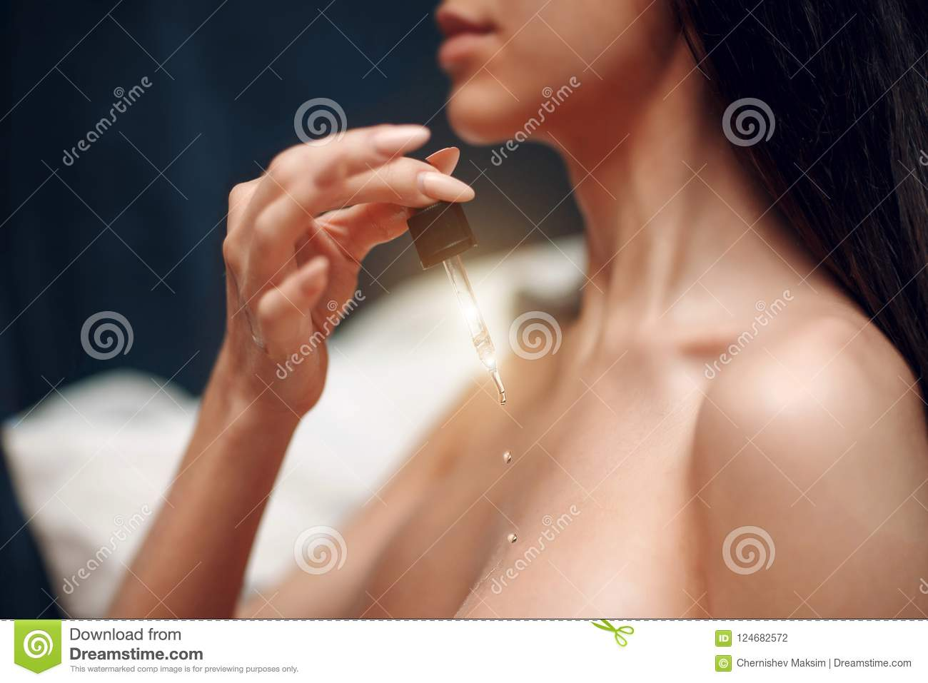 A young girl holds a pipette with cosmetic oil. Skin care concept.