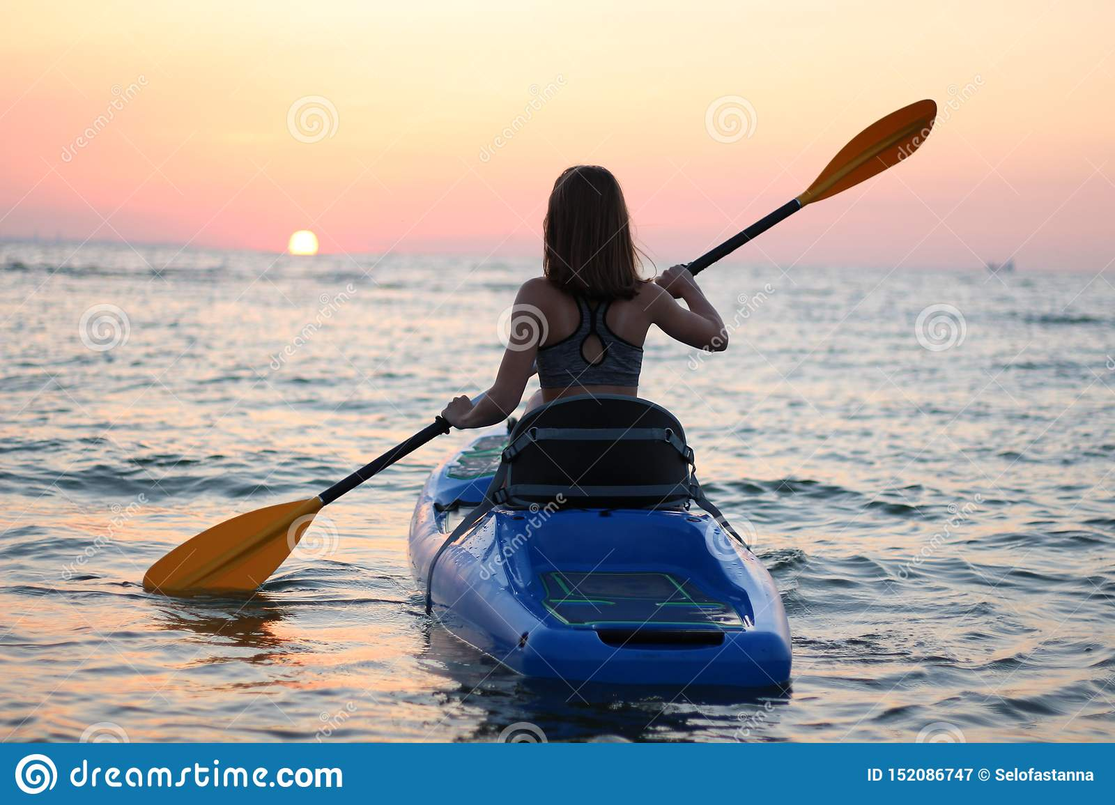 Young girl on the kayak greets the dawn of the sun