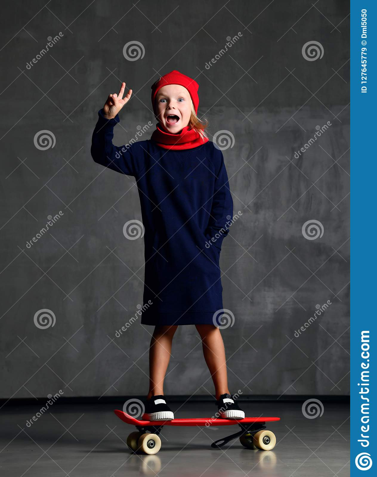 Young girl kid standing on skateboard in blue coat and red scarf and har showing peace sign screaming