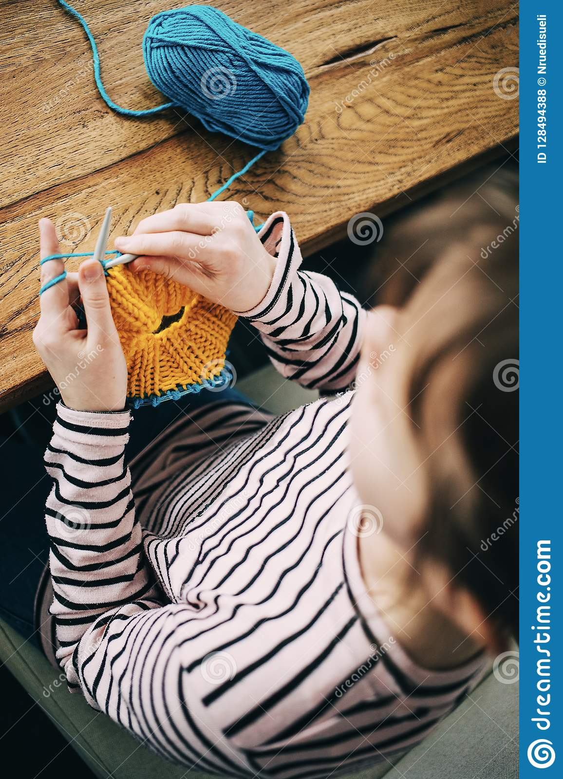 Young girl knitting a circle scarf. Learnig knitting basics.