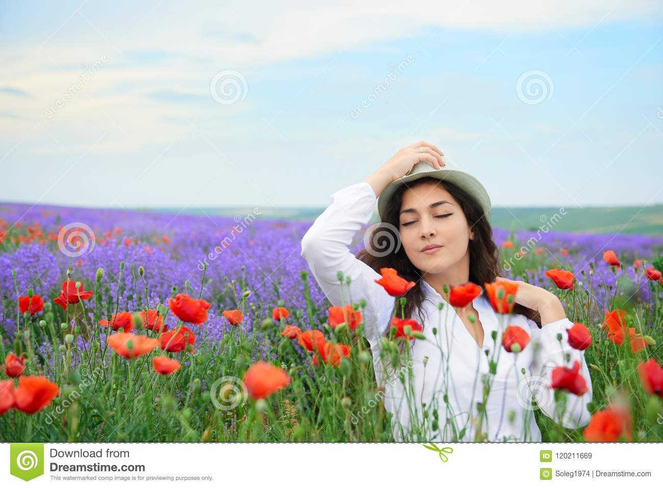 Young girl is in the lavender field with red poppy flowers, beautiful summer landscape