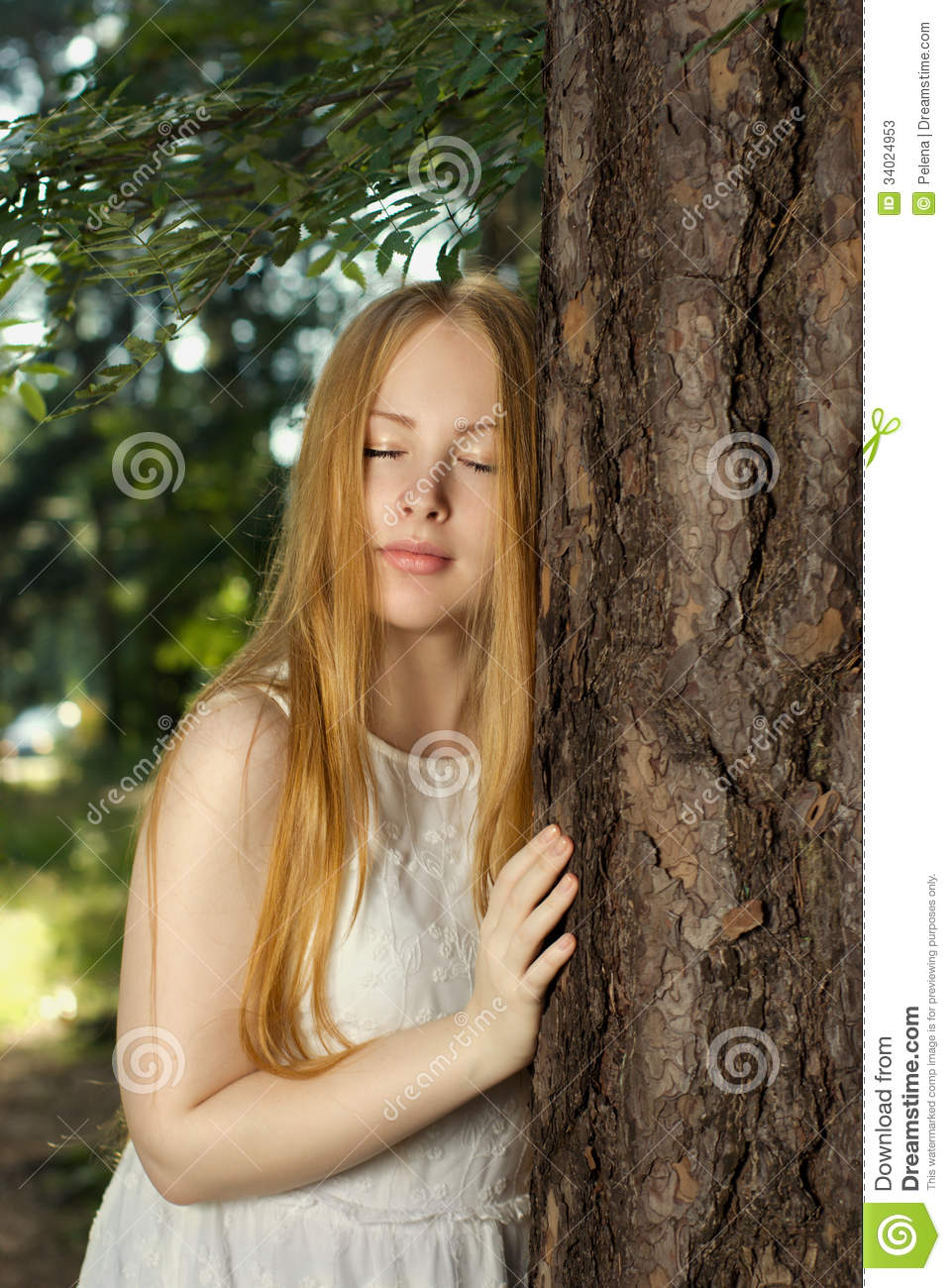 A Young Girl With Long Blond Hair Standing In The Forest