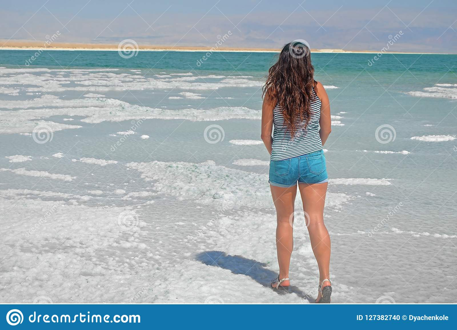 Young girl looking into the distance to the mountains. brunette walks on the islands from salt in the dead sea, Israel.