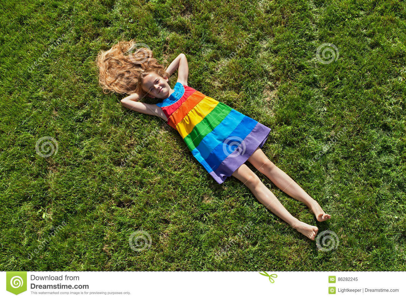 Young girl on lying on freshly mowed lawn