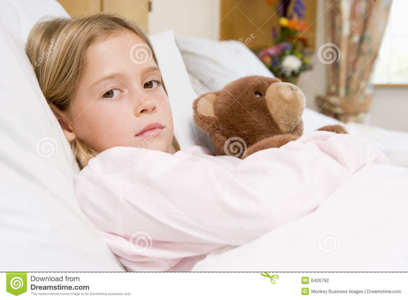Young Girl Lying In Hospital Bed With Teddy Bear Stock