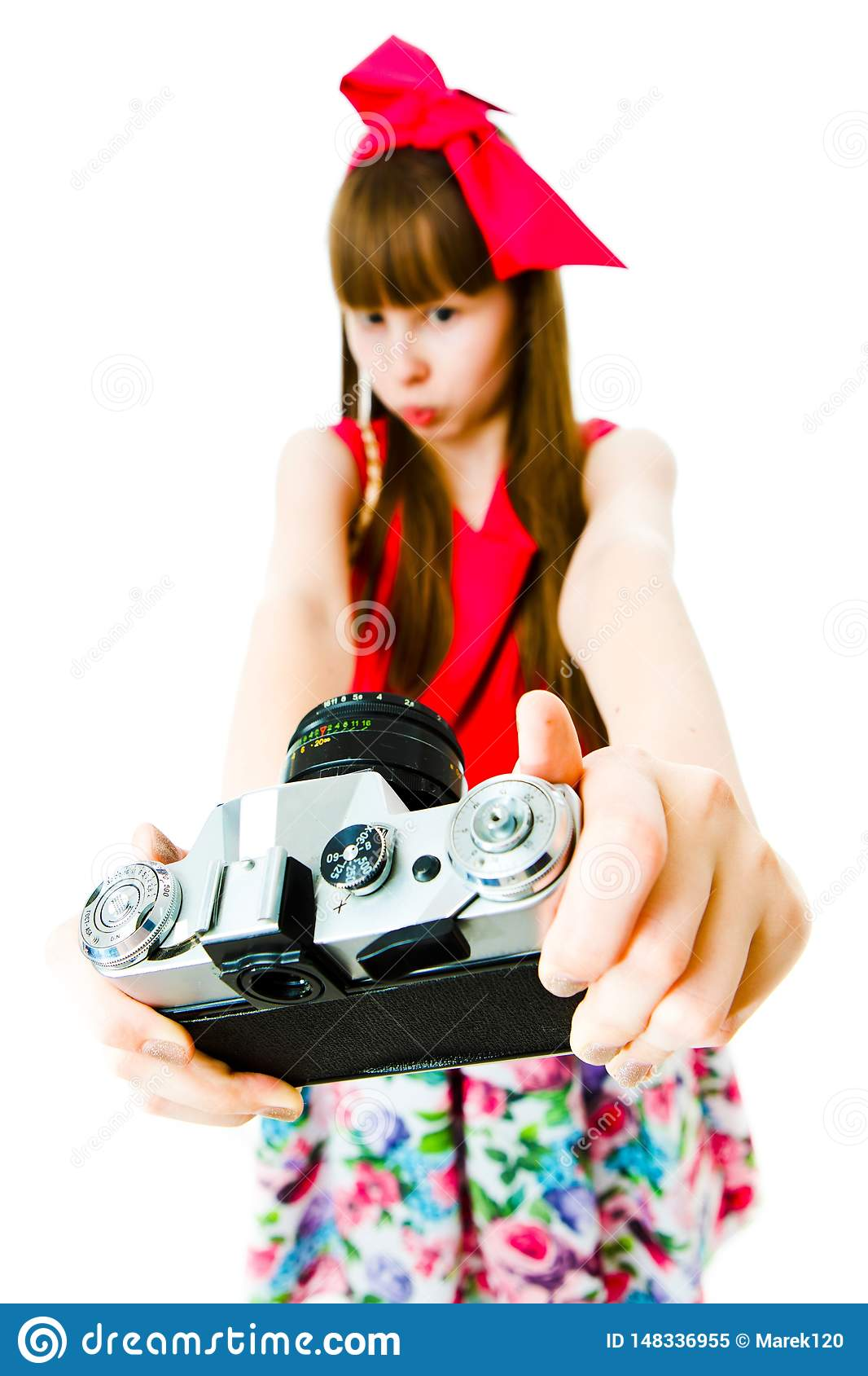 Young girl in magenta dress and ribbon in hairs taking selfie - vintage camera