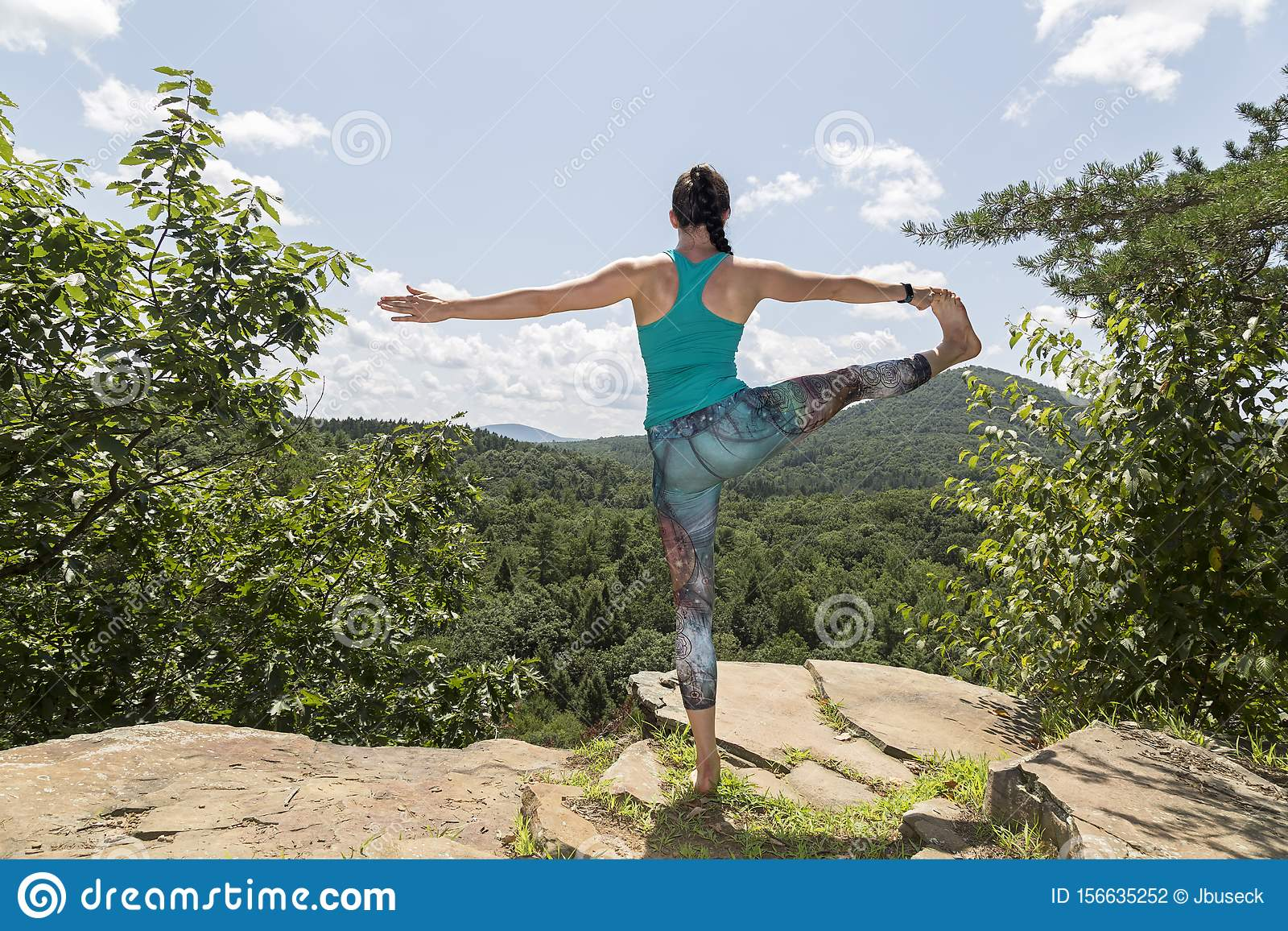 Young girl meditating with yoga on a mountain cliff