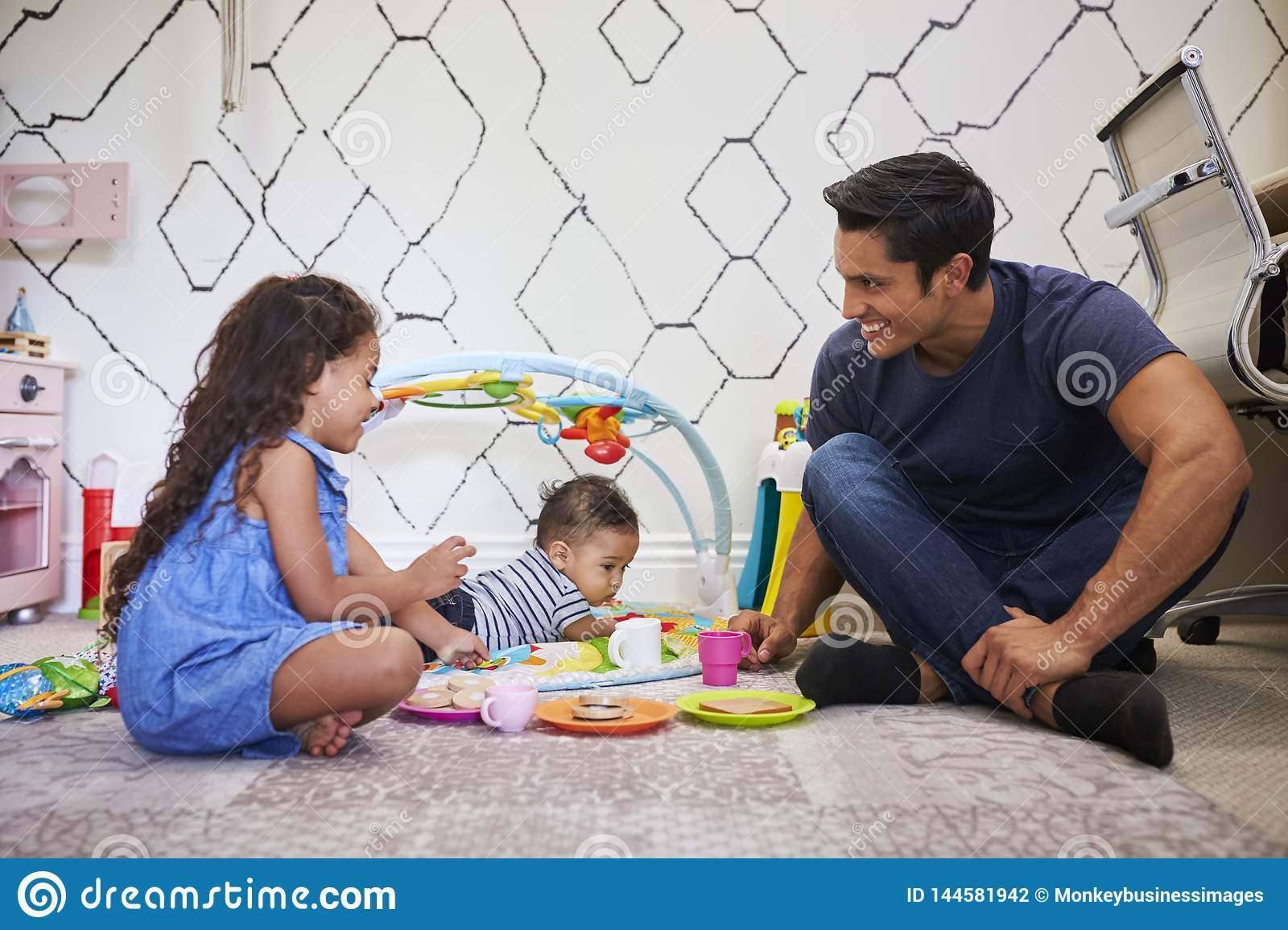 Young girl playing tea party with dad, sitting on the floor, baby brother on a play mat beside them