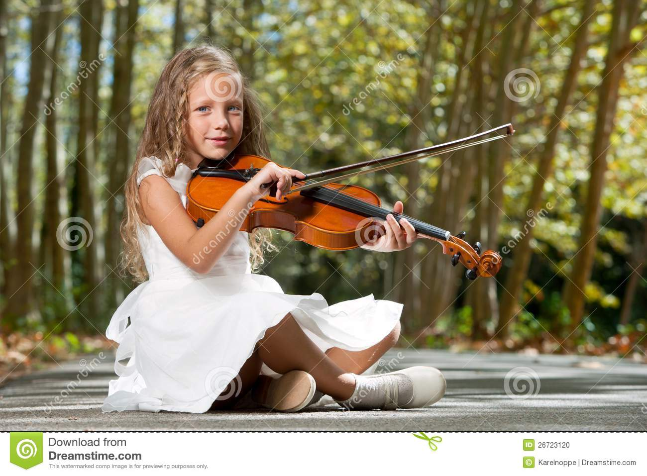 young girl playing violin in the woods stock photo