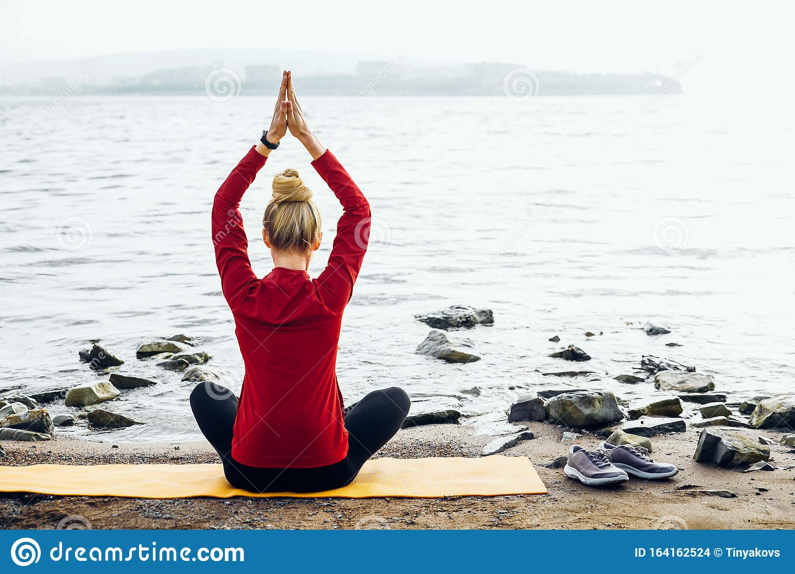 Rear View Of Young Woman Sitting In Lotus Position On The
