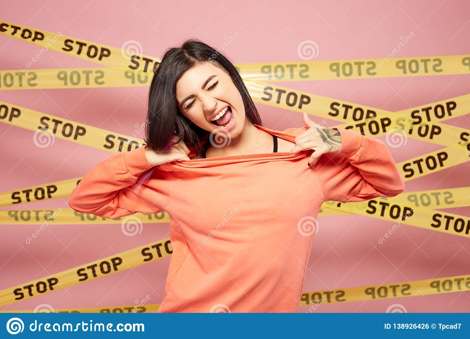 Young girl with purple hair tips dressed in peach color sweatshirt shouts on the background of pink wall with the yellow