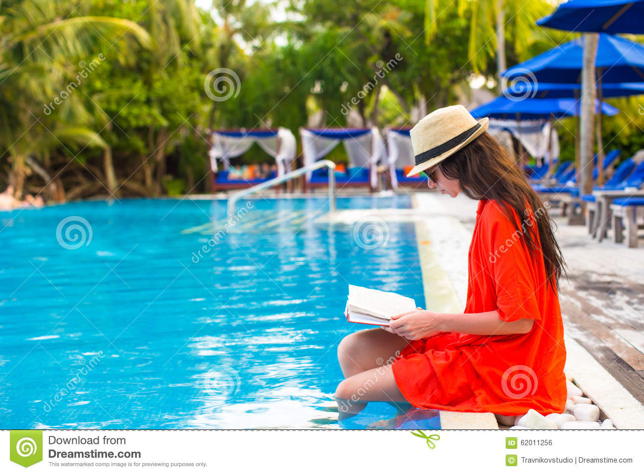 young girl reading book relaxing in swimming pool stock photo image 62011256