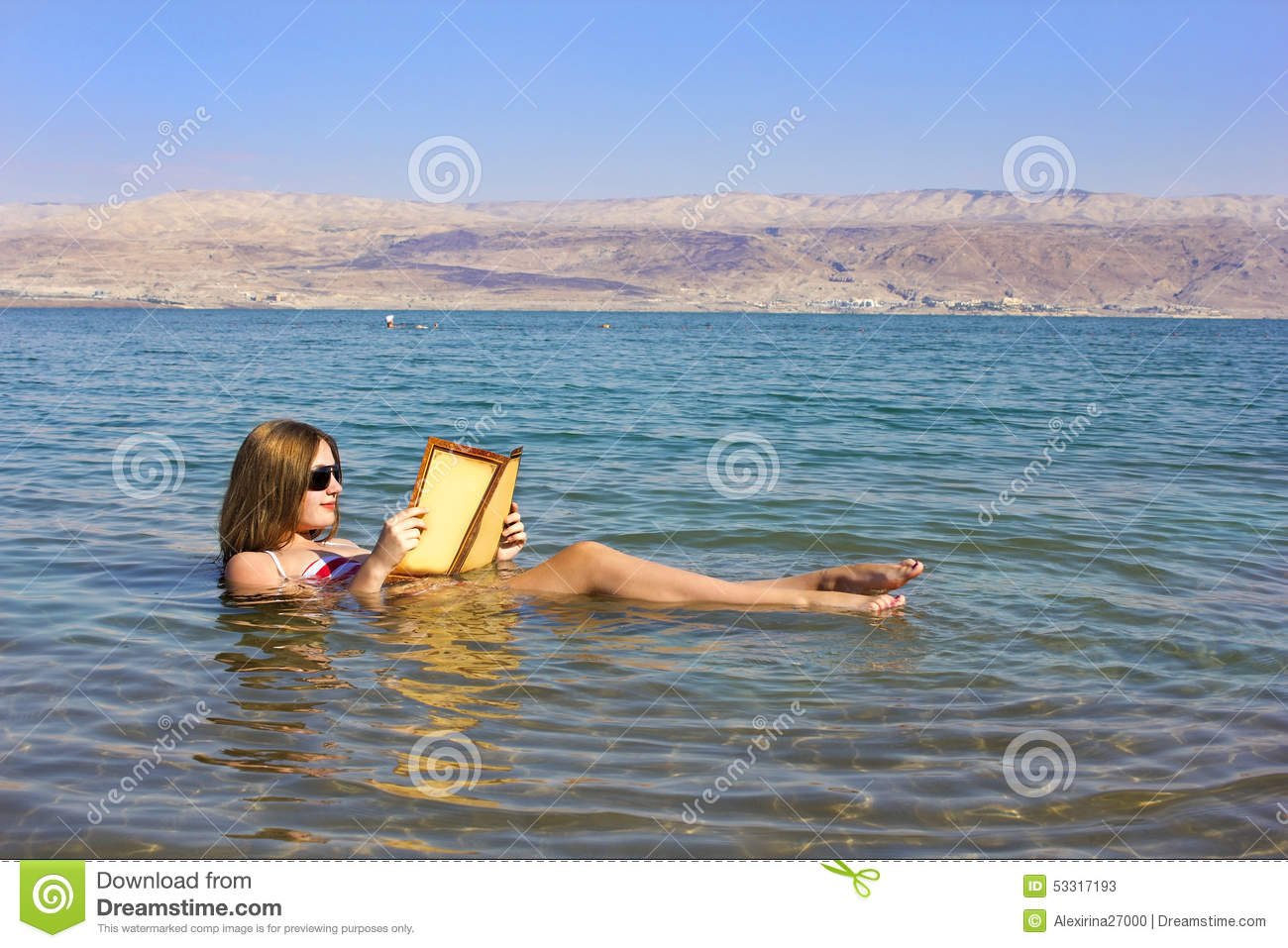 Young girl reads a book floating in the Dead Sea in Israel