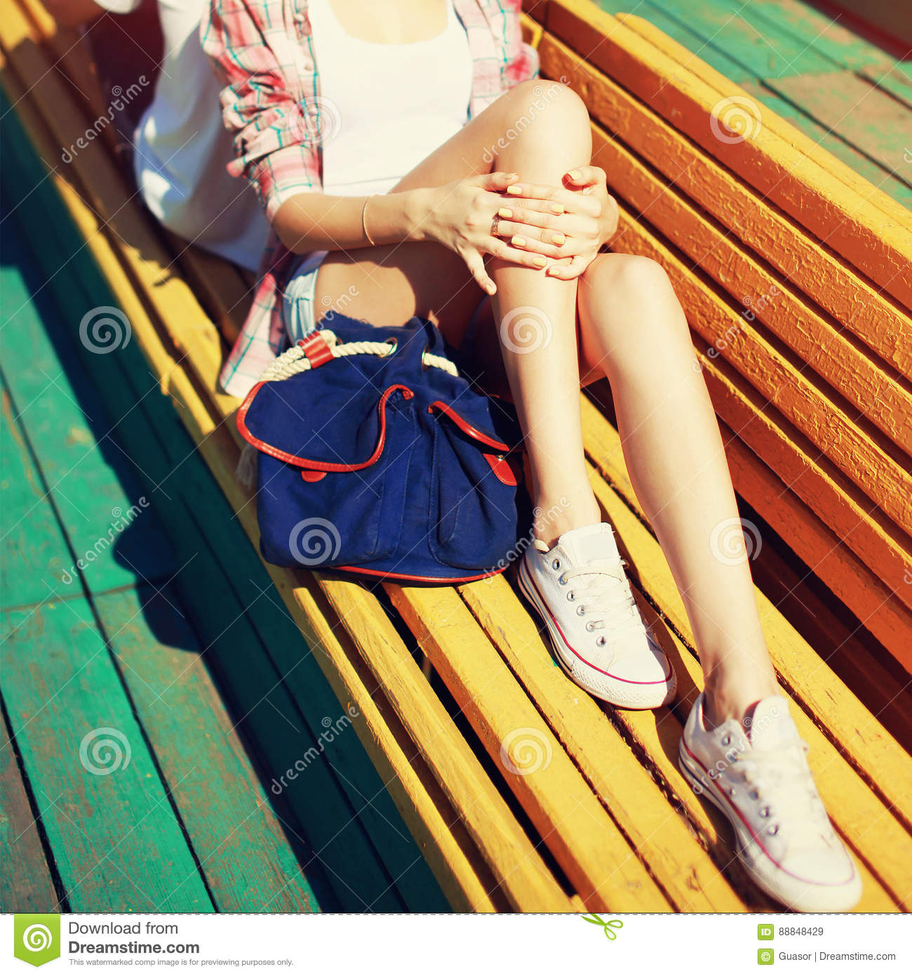 Young girl resting in city park on bench, beautiful slender female legs at summer