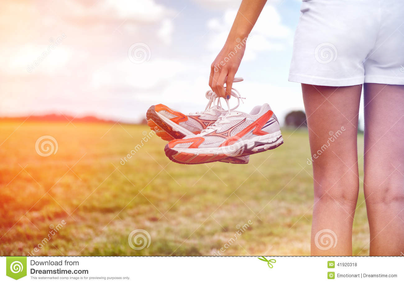 Young girl in shorts holding her sneakers